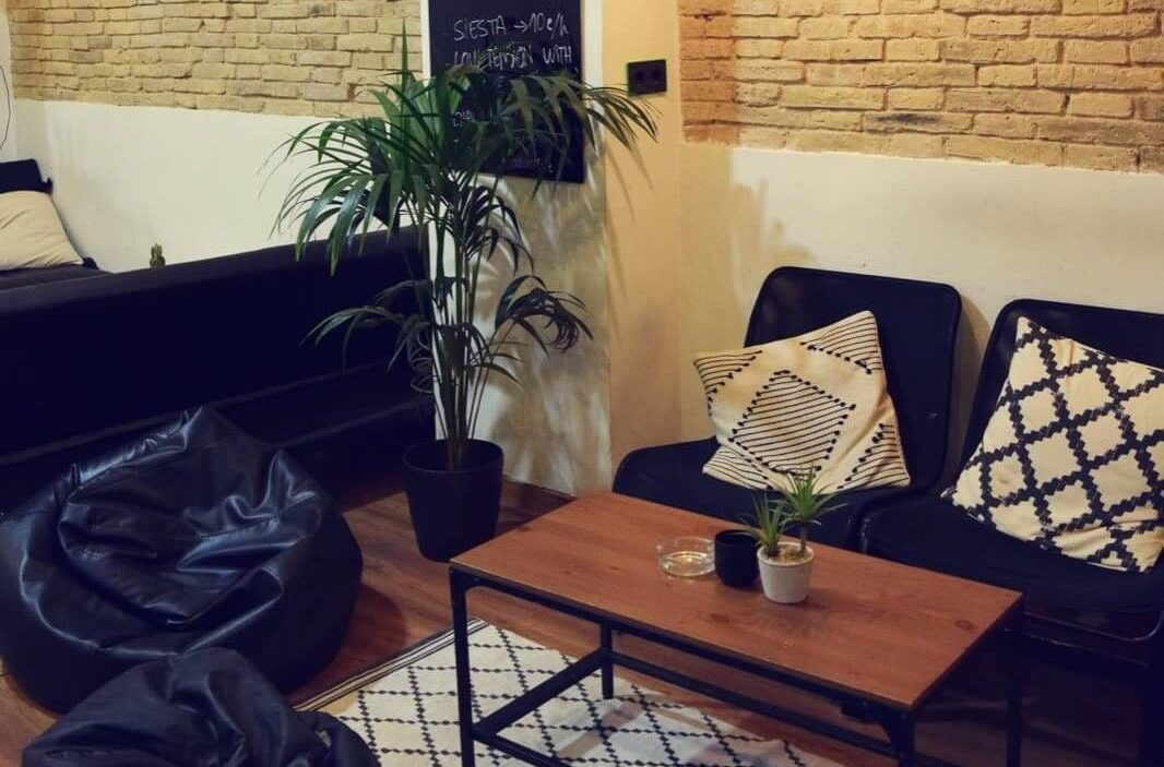 barcelona weed club chilling area with chairs cushions table and plants
